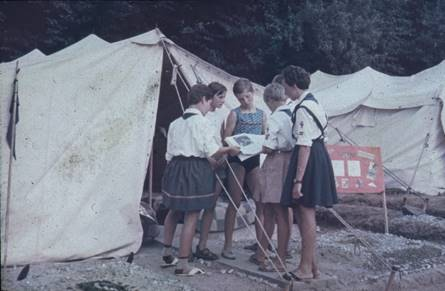 A group of people standing in front of a tent  Description automatically generated